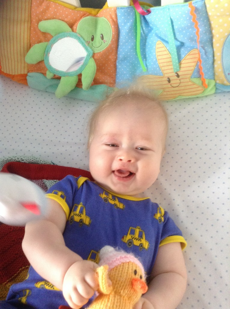 lucas as a baby looking up at camera smiling wearing a blue top with yellow cars on