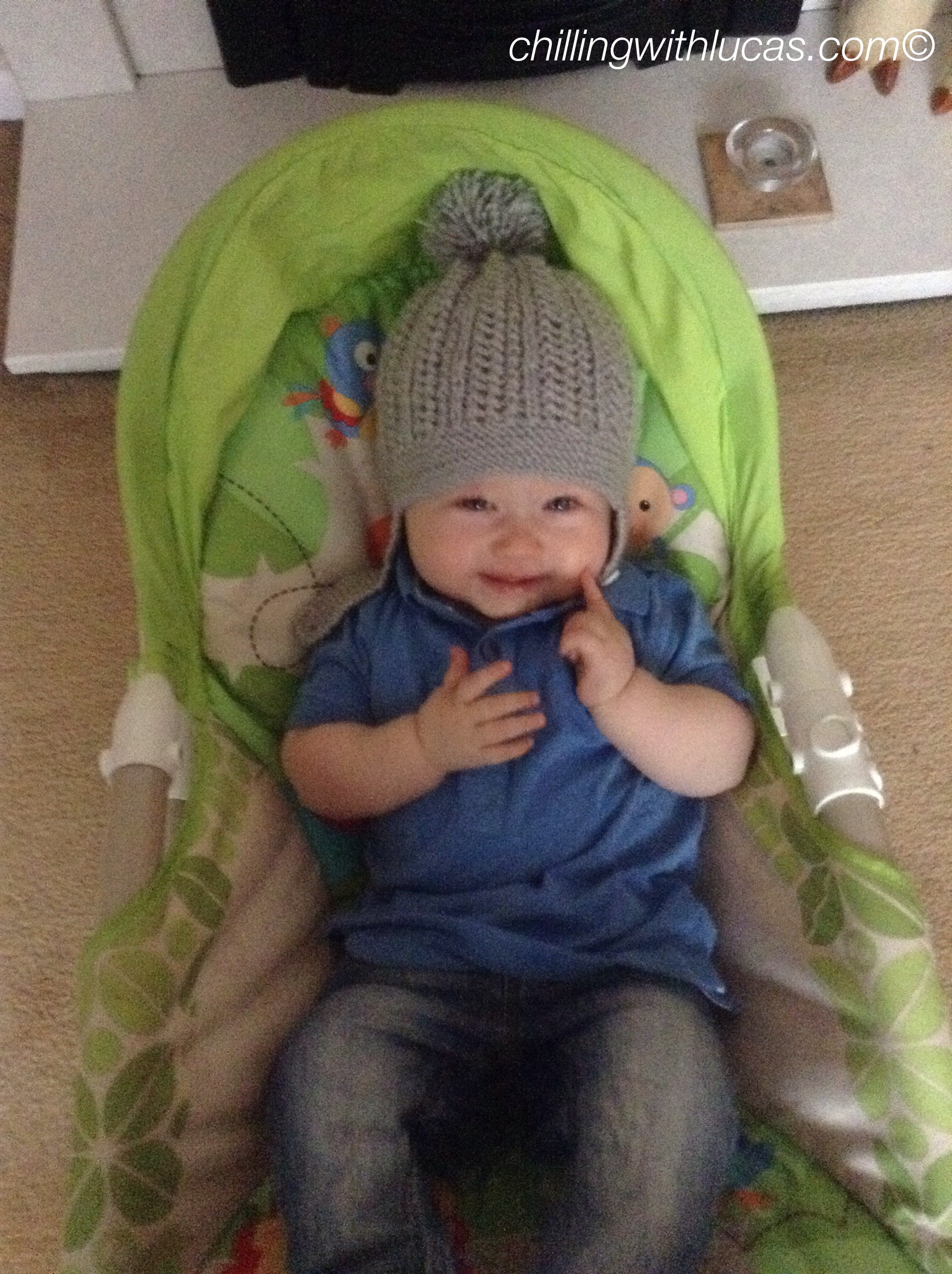 lucas is sat in his chair looking up at the camera wearing a blue polo shirt, faded jeans and grey knitted hat