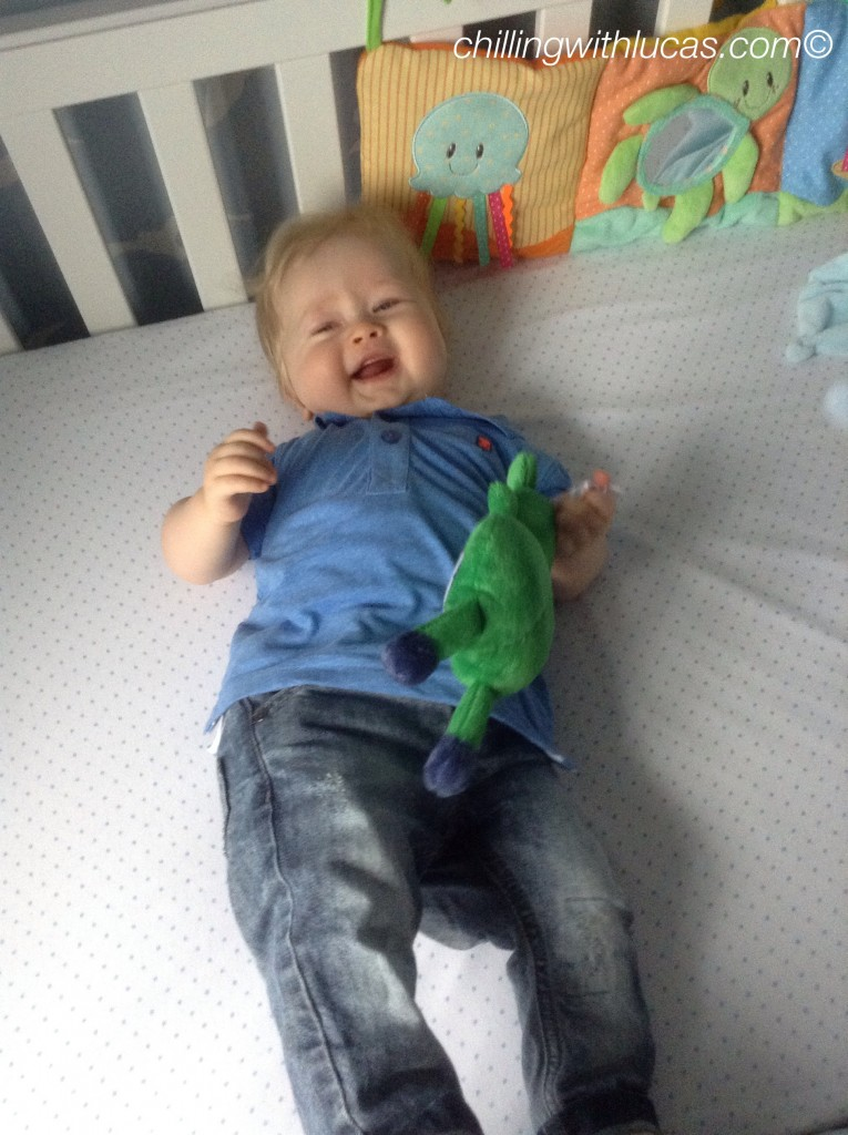 lucas is led in his cot looking up and smiling wearing jeans and a blue polo shirt