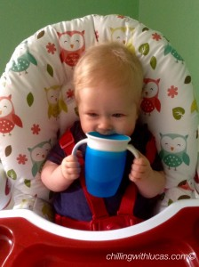 Lucas biting on the blue munchkin cup
