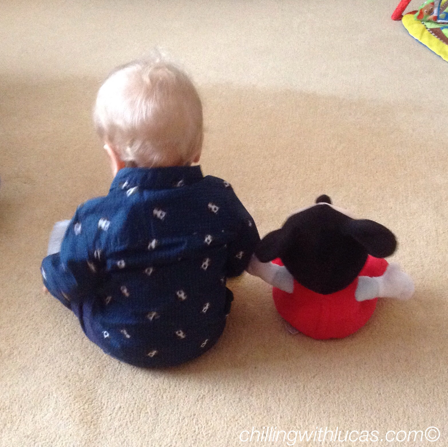 lucas is a baby with blonde hair, he is sitting up wearing a navy shirt and mickey teddy next to him