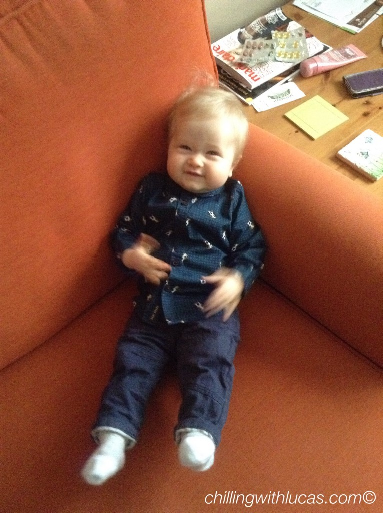 Lucas is sat up on the sofa looking at me. He is wearing a navy print shirt and navy trousers