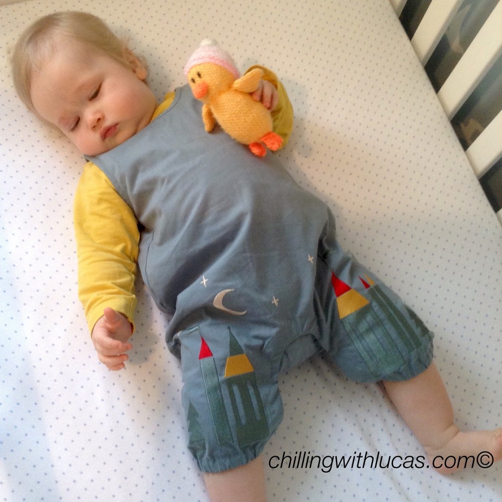 Lucas wearing enchanted castles Little Green Radicals dungarees lying in his cot