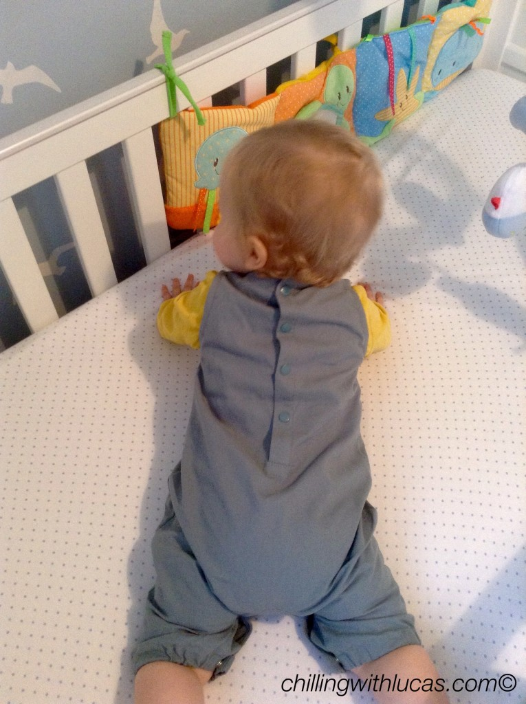 Lucas wearing Little green radicals anchanted castles dunagrees. He is led on his front in the cot so you can see the buttons down the back