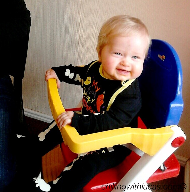 lucas sat in a highchair smiling and wearing a halloween baby growHalloween