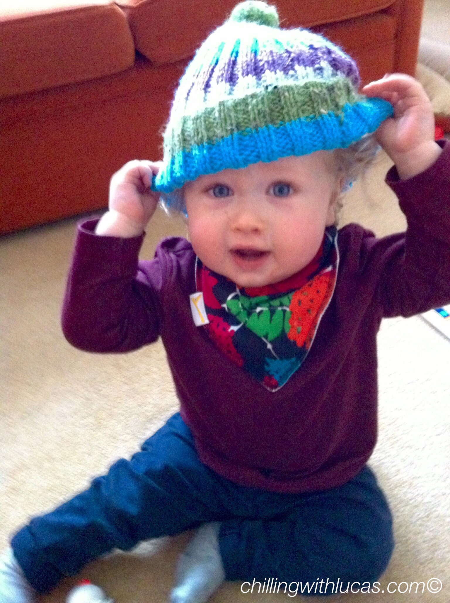 Lucas wearing a multicoloured funky giraffe bib, knitted hat, maroon top and navy jeans. He is sat down looking at the camera with his hands stretching his hat