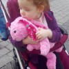 A 4 year old girl sat in her pram holding a pink bunny teddy.Autism and pica awareness