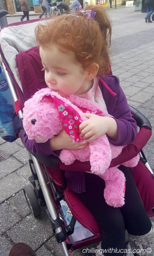 A 4 year old girl sat in a pram holding her pink bunny teddy. Autism and pica awareness