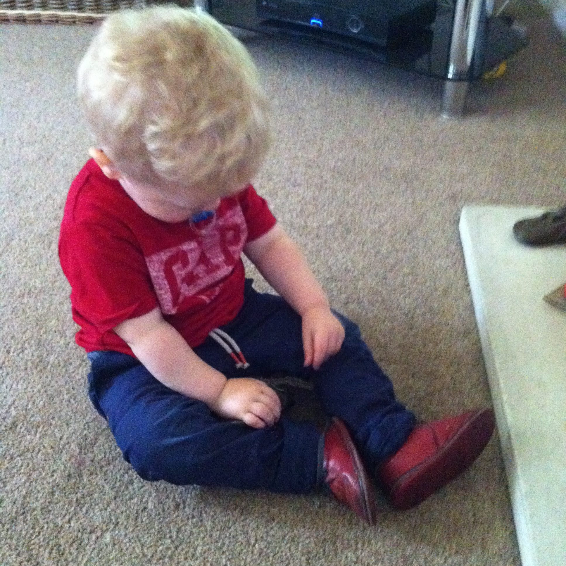 Lucas looking down at red shoes he is wearing. They are his uncles first shoes. Lucas is wearing a red gap t shirt and navy pants