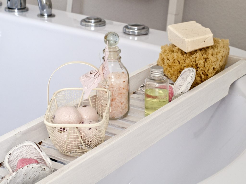 Parents relax around the home. A photo of a bath with bath bombs and bottles of bath oil. A relaxing neutral scene