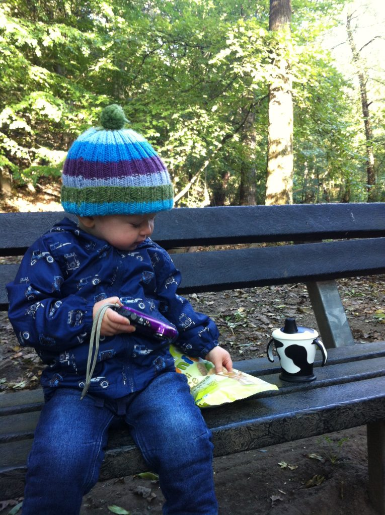 #mamiadaysout lucas sat of a bench in woodland with a stripy bobble hat, blue jacket with a car pattern and dark blue jeans. His legs dangling off. His face looking down to the side as his hand reaches into a pack of mamia rice cakes