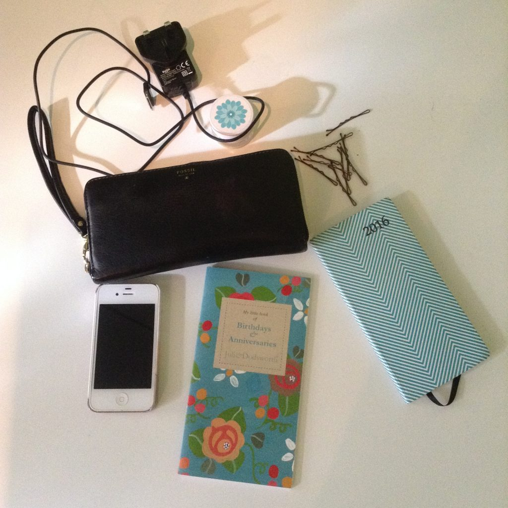 Blogtober, what's in my bag. Photo of white iPhone 4, julie Dodsworth floral birthday book, white and green stripy diary, black phone charger, brown kirby grips, black leather fossil purse, lip balm