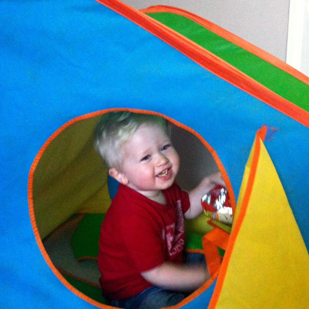 Blogtober 4 share a secret about yourself photo of Lucas smiling through thevwindow of his blue, orange yellow and green tent