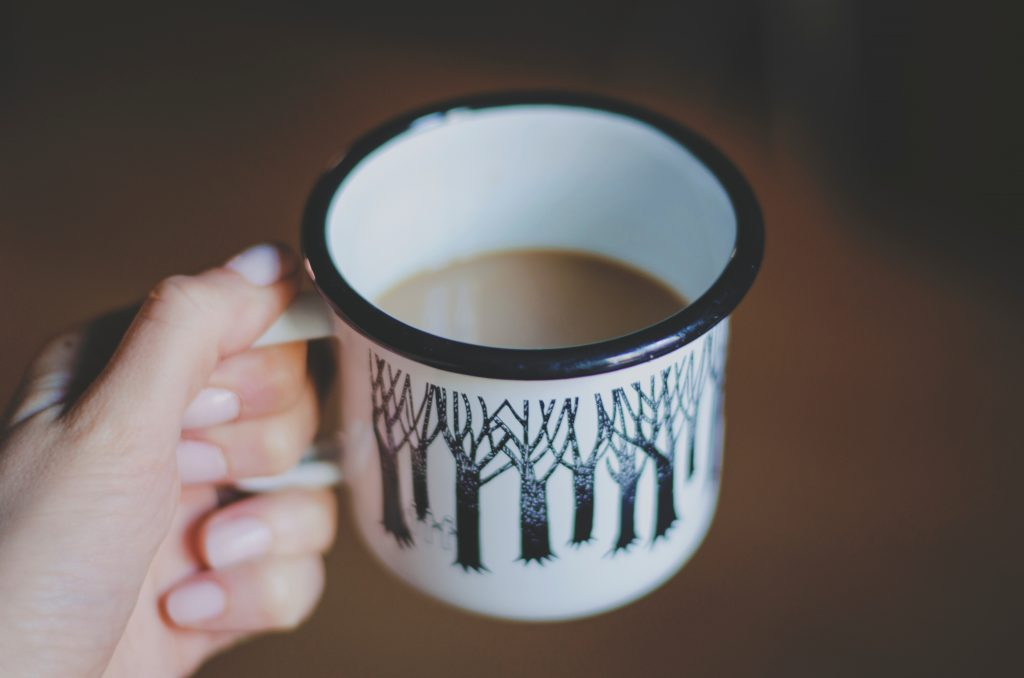 what mummy really wants for christmas. a cup of coffee. white mug with black trees on it filled with coffee being held