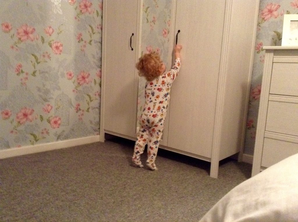 Ordinary moments Lucas reaching up to black handle on white wardrobe with floral wallpaper in the background and grey carpet