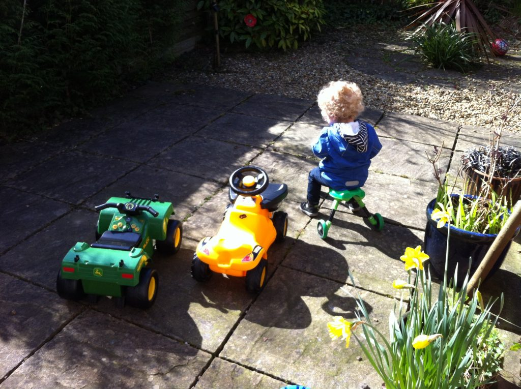 Lucas sat on green skuttlebug weaing a blue jacket, blonde curly hair. On flagged garden with pot of daffodils behind him, next to him is a yellow jcb ride on toy and green john deere atv ride on toy