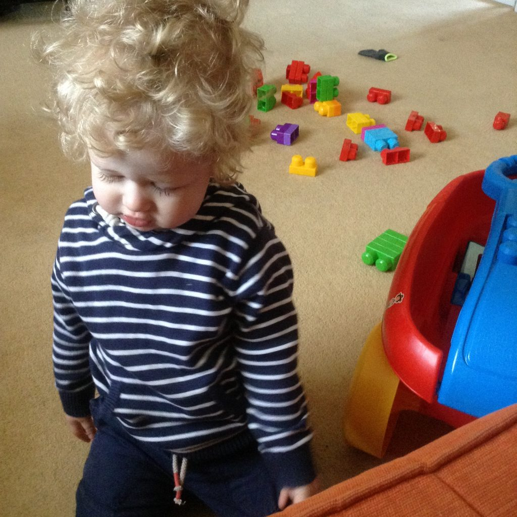 Happy days Lucas in a blue and white striped hooded top, looking down with a slight smile and big blonde curly hair. Megablocks are scattered on the carpet behind him
