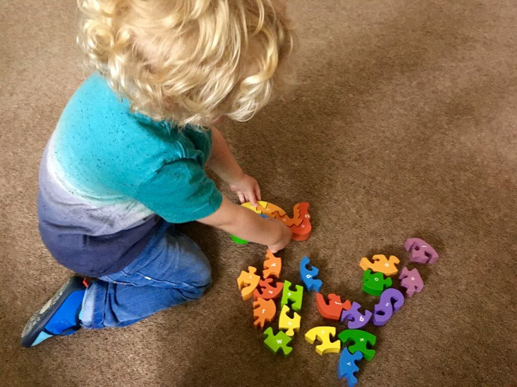 Wooden toys Lucas playing with a bright colour alphabet snake