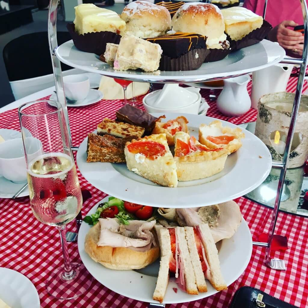 Bolton food and drink festival review A three tier stand filled with cakes and sandwiches on a red and white checked tablecloth with a glass of prosecco at the side