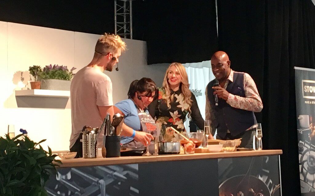 Bolton food and drink festival review John Whaite, Alana spencer, Ainsley Harriet and Rosie Dummer stand on stand around a cooking worktop talking to each other