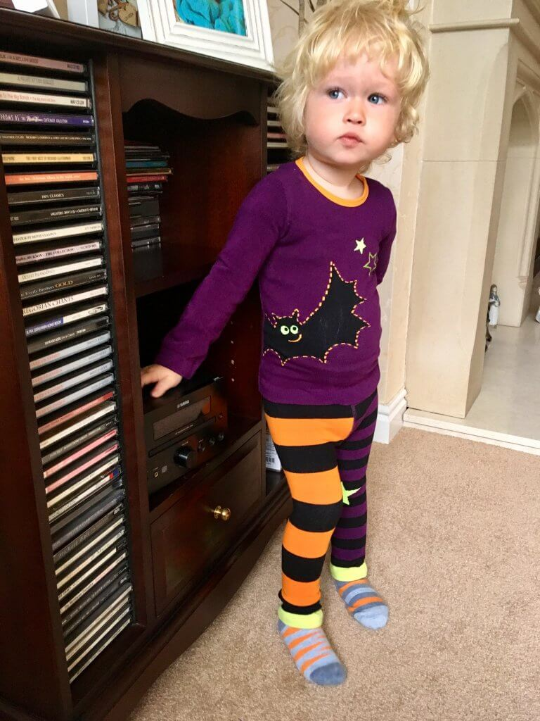 Blade and Rose Halloween set Lucas is wearing the knitted outfit which is a purple top with a black bat on it with orange and black stripy leggings. He is stood against a cd cabinet full of cds and a CD player. Lucas has blonde curly hair