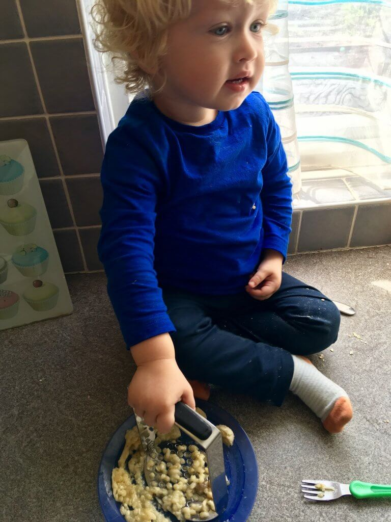 Savoury flapjack recipe Lucas is sat on a grey worktop mashing bananas