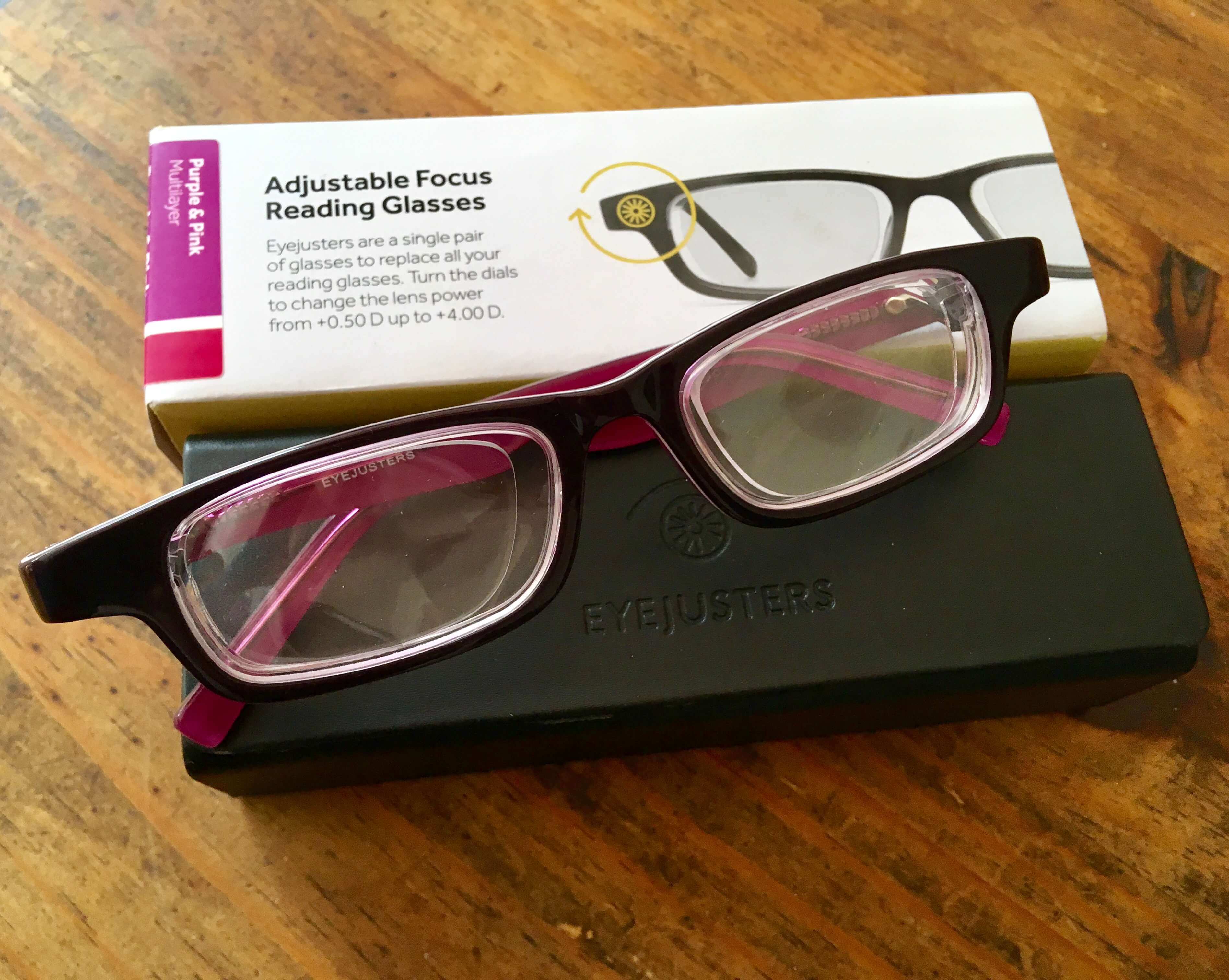 Eyejusters review purple glasses against a black case with white packaging on a wooden backfround