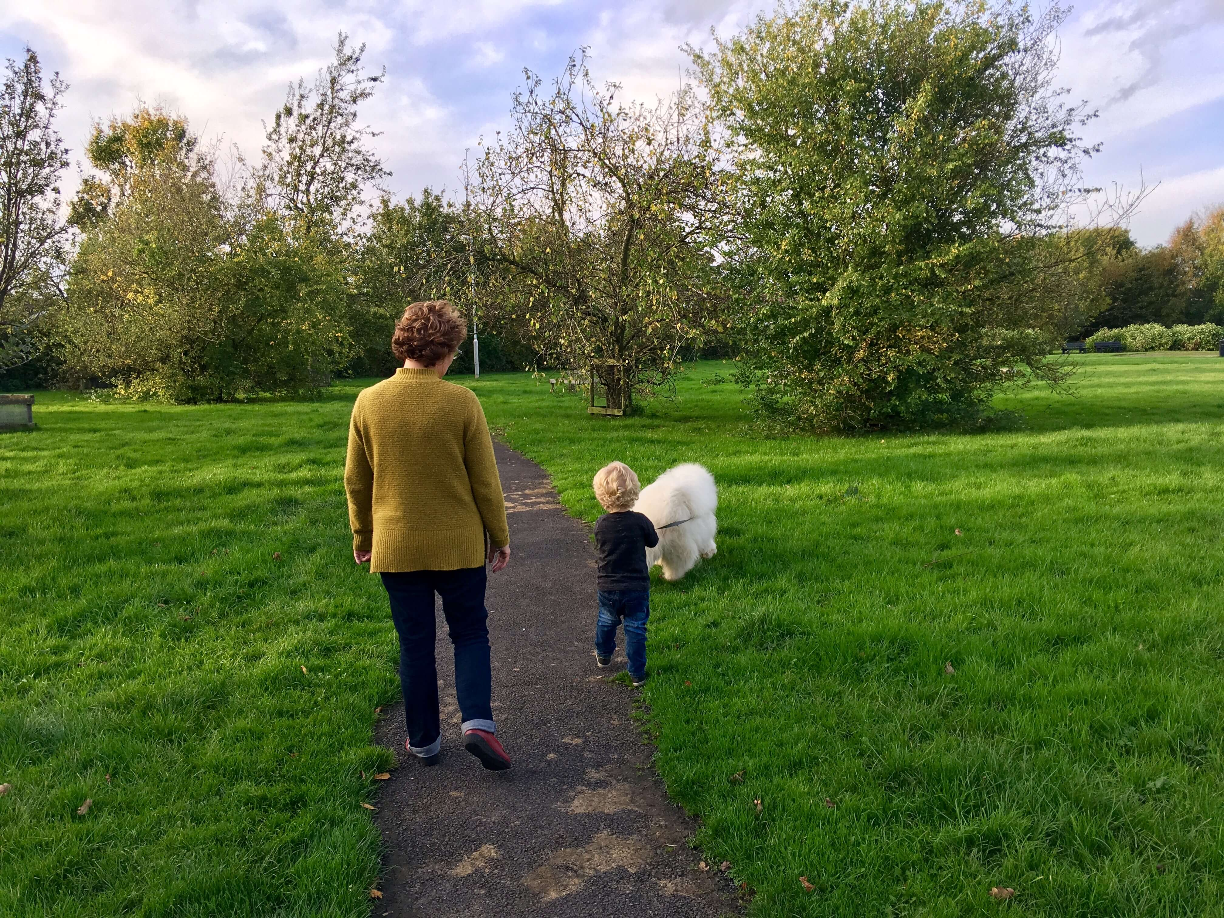 Walking the dog my mum and Lucas walking a big white fluffy dog through the field. My mum has a mustard coloured jumper in with dark blue jeans, short brown curly hair. Lucas has short wavy blonde hair holding the dogs lead and wearing dark blue jeans and black long sleeves top