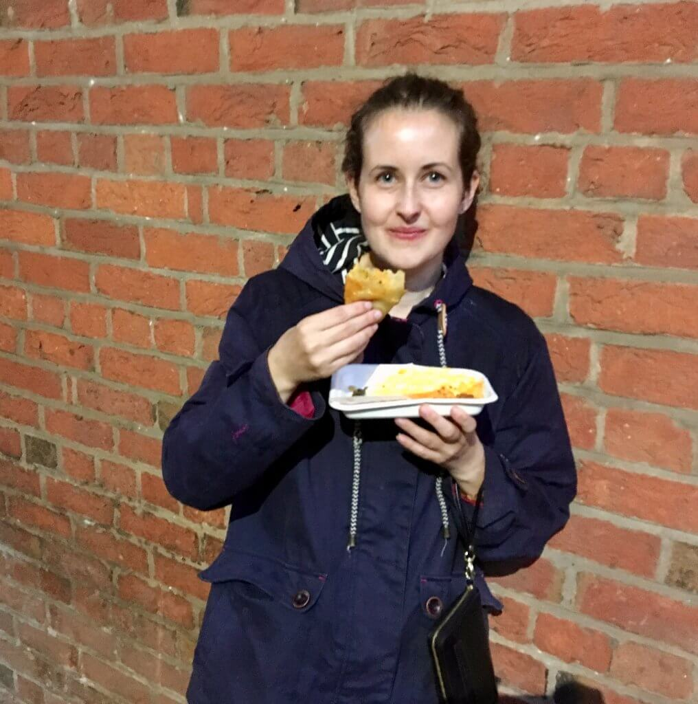 Haigh foodie Friday review I am stood next to a brick wall eating holding a samosa out of a polystyrene tray