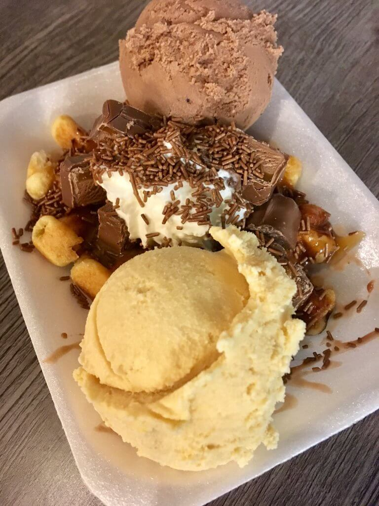 Haigh foodie Friday review a polystyrene tray with a scoop of vanilla ice cream and a scoop of chocolate ice cream with waffles in the middle topped with broken mars bar and cream