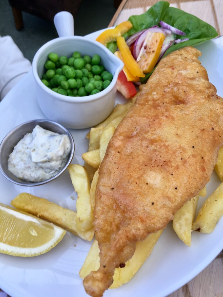 Birkacre garden centre restaurant, Coppull. A battered fish sat on a bed of chips with peas, a lemon and tartar sauce at the side