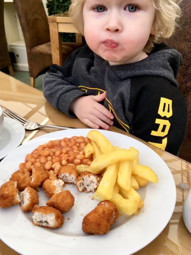 Birkacre garden centre restaurant, Coppull. Lucas sat wearing a black batman hoody looking at the camera with blonde hair, blue eyes, mouth closed full of food. In front of him is a plate of chicken nuggets, chips and beans