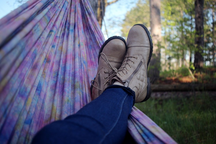holiday whilst pregnant. A lady's legs from the knees to feet lying in a purple hammock wearing dark blue denim jeans and brown boots