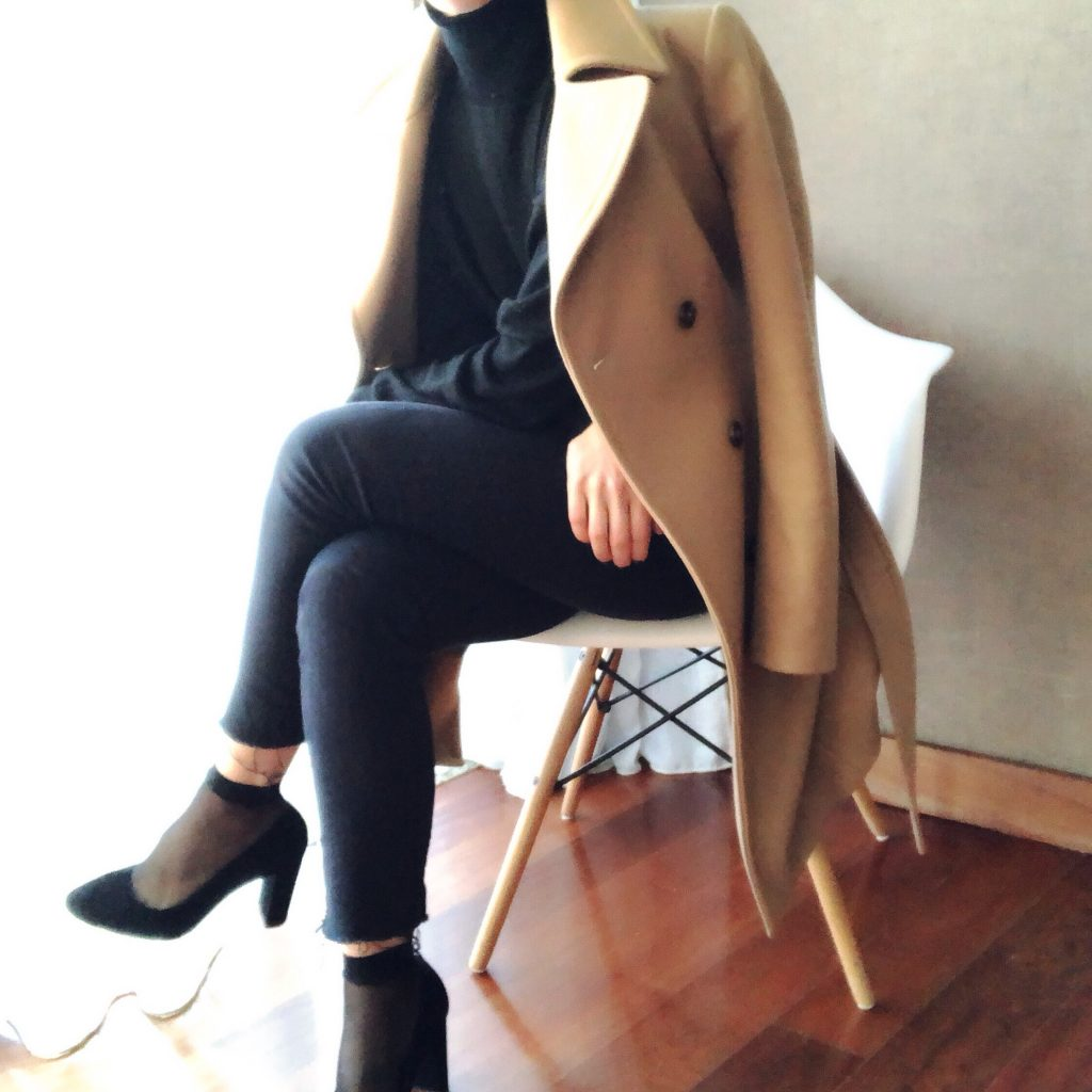 Fashion essentials worth investing in for 2018. a woman sitting down on a white chair when wodden legs. She is wearing black heels and pop socks, dark skinny jeans, a black poloneck jumper with a camel coat draped over