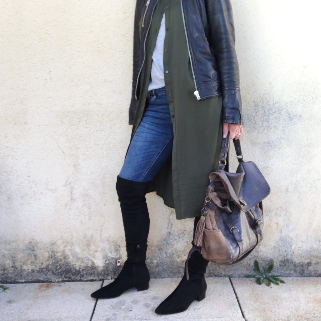 Fashion essentials worth investing in for 2018. A woman wearing a black leather kacket with a long line khaki top underneath, layered over a neutral top. Denim skinny jeans and over the knee black boots. She is holding a metalic bag and standing against a grey wall on grey flagged flooring