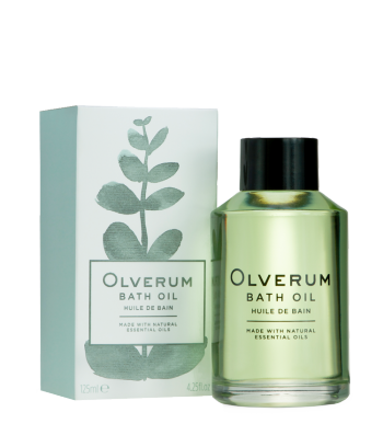 Valentines gift ideas a lareg bottle of olverum bath oil, a clear bottle with simple black writing and a black lid. Next to it is the olverum box with is white with simple greeen writing and green leaf running up the box