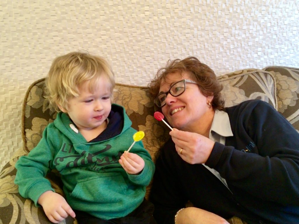 Zollipops a photo of my mum and Lucas sat on the sofa, they both have a lolly in their hand.