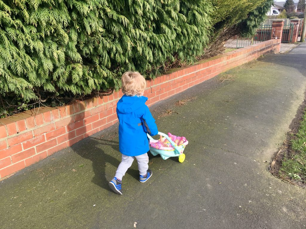 Baby Born Interactive Doll Lucas is walking down the street wearing a blue coat and. Grey jogging pants pushing the blue and pink dolls pram