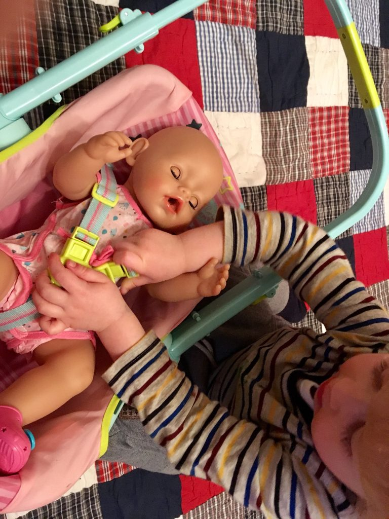 Babu Born Interactive Doll Lucas is sat over the Doll who is in her carry seat as Lucas fastens the straps