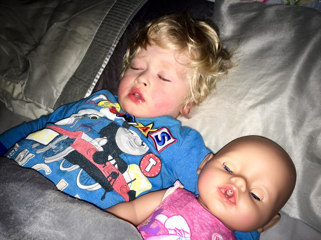 Baby Born Interactive Doll Lucas is asleep on his back in bed wearing blue thomas the tank engine pyjamas whilst the Doll is asleep next to him, both of them under silver bedding