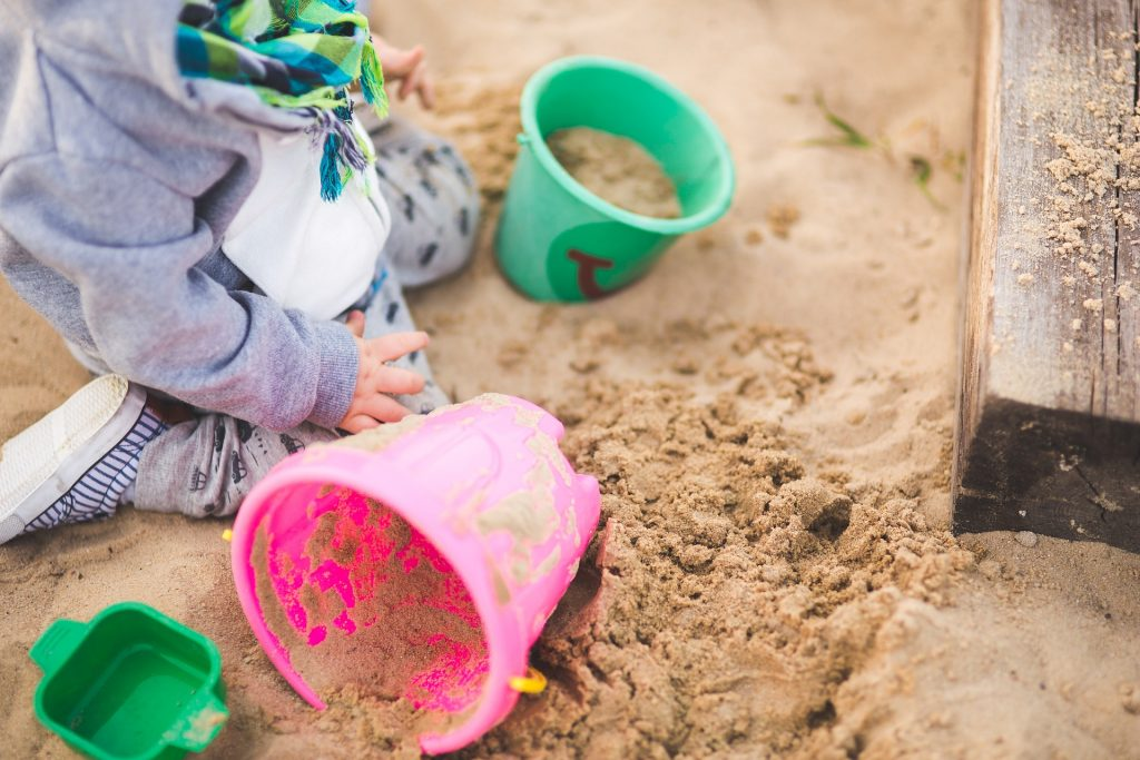 The best toys to get children outside sand with a child kneeling and two buckets