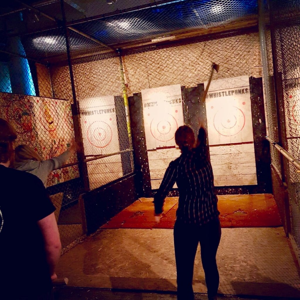 Whistle Punks axe throwing I amthrowing an axe at the board, the axe is mid air