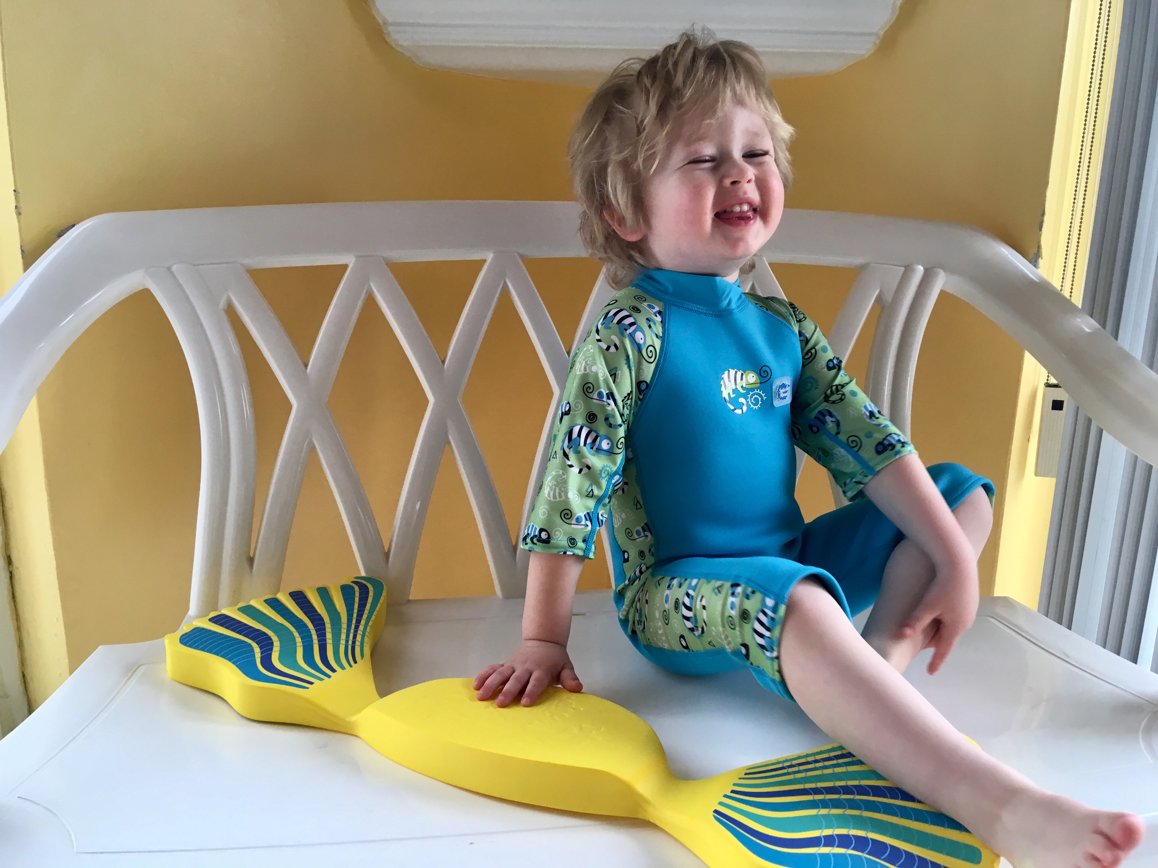 The benefits of learning to swim at a young age. Lucas sat in a bench laughing wearing a blue and green all in one sun suit