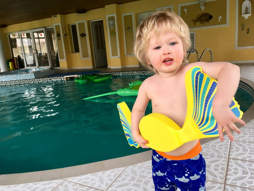 The benefits of learning to swim when young. Lucas is stood with a pool behind him. He is wearing blue swim shorts and holding a yellow and blue float
