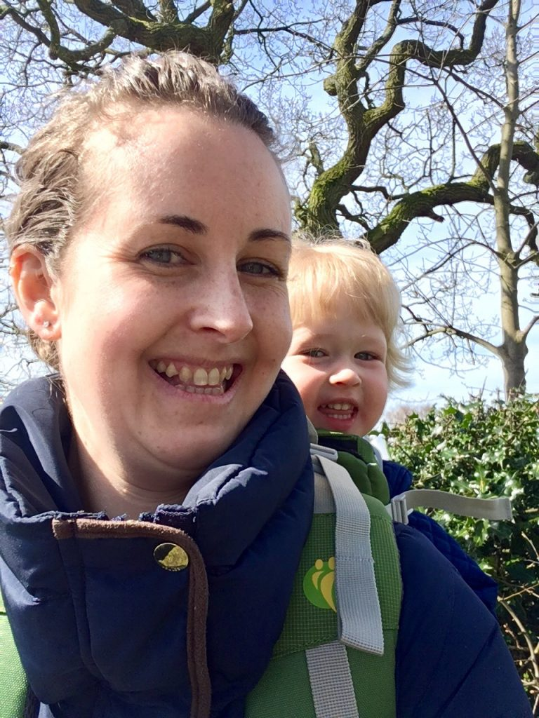 LittleLife Adventurer S2 review the photo is a close up of me smiling at the camera. My hair is tied up, you can see the top of my navy coat and the green child carrier straps on my shoulders. Lucas is smiling behind me looking at the camera. He is sat in the carrier