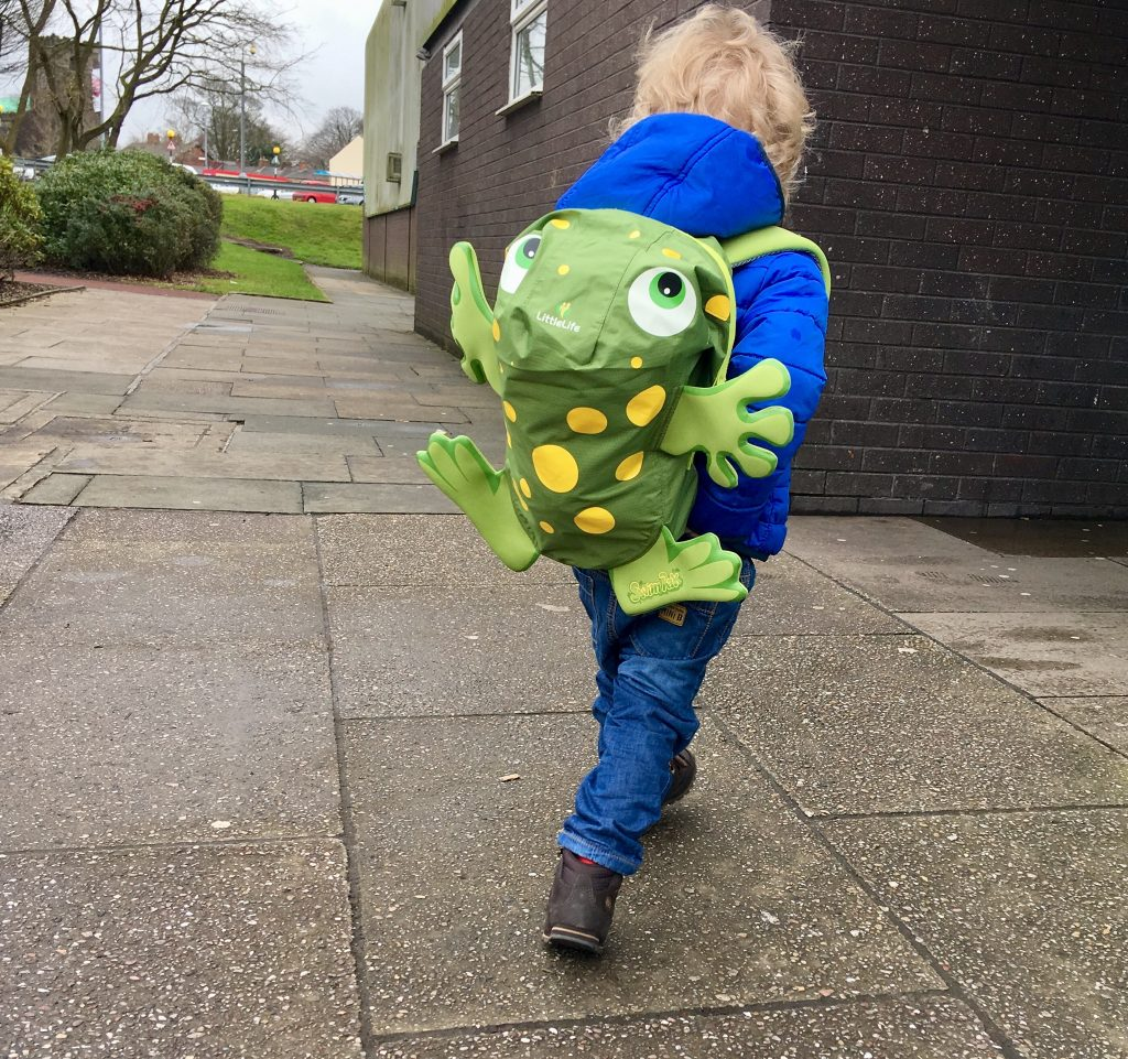 LittleLife swim bag. Lucas is walking with a blue coat and jeans on. On his back is the frog swim bag