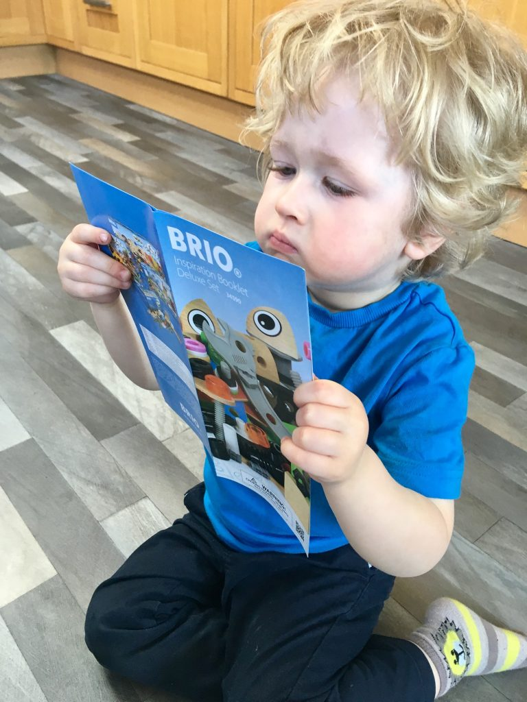 BRIO builder deluxe set Lucas is sat with a serious face looking at the brio leaflet. He is sat on a grey floor