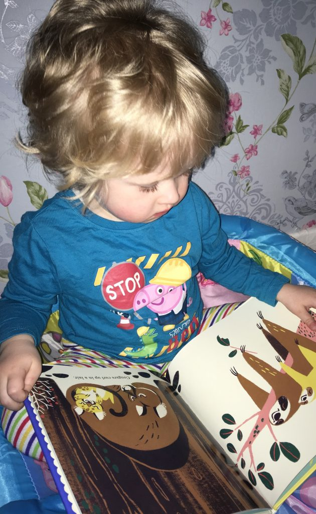 Bath, book, bed (and maybe a little creativity) Lucas is sat up wearing Peppa Pig pjs and looking down at a book
