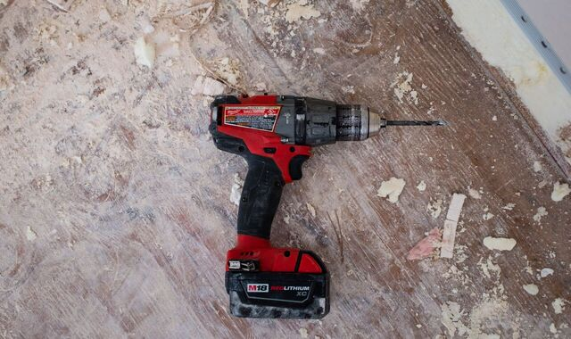 Save money long term. A picture of a red drill led on its side on a wooden floor