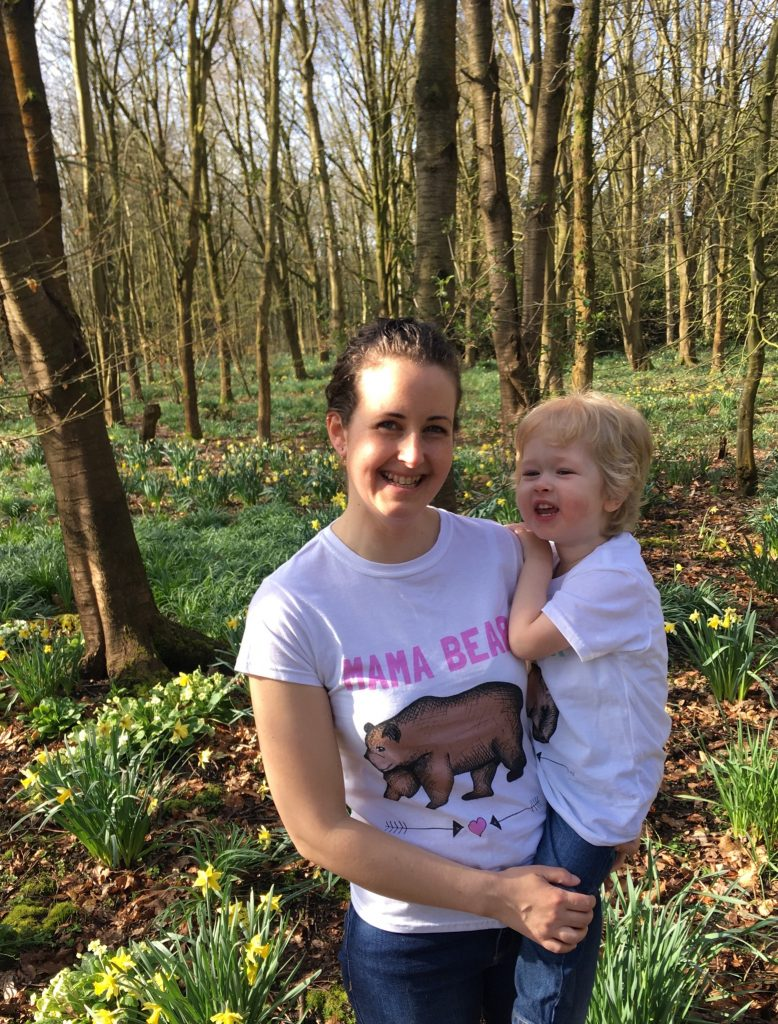 Mama Beat and Bear Cub t-shirts a photo of me wearing the Mama Bear Tshirt holding lucas who is wearing Bear Cub t-shirt. We are stood in a field full of daffodils and trees